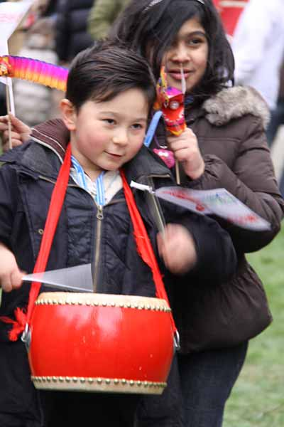 Child with red drum at Chinese New Year in London