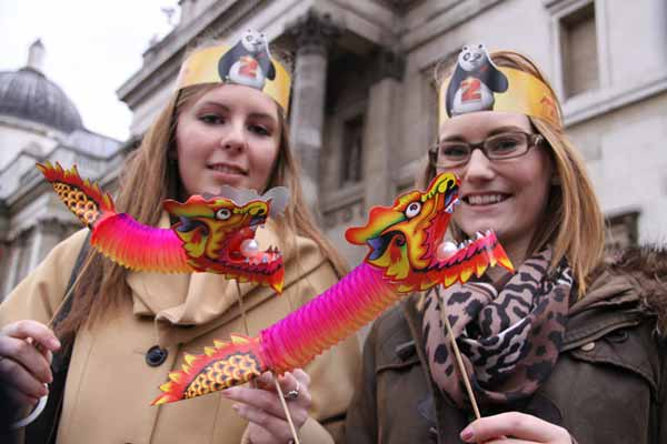 Women holding paper dragons at Chinese New Year in London